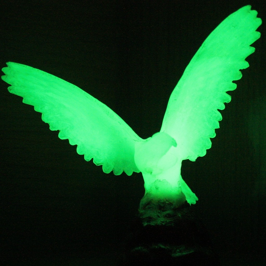 Aigle luminophore en verre teinté par une terre rare phosphorescente. Après avoir été éclairé, il continue à émettre de la lumière dans l'obscurité.